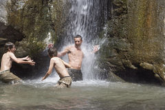 Father With Sons Playing Under Waterfall Stock Image