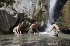 Father With Sons Playing Under Waterfall Royalty Free Stock Photos