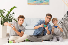 Father and sons playing video games Stock Images