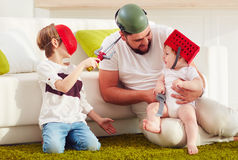 Father with sons playing in war games at home Stock Image