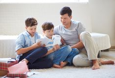 Father with sons. Portrait of cute boys and their father looking through pictures at home Royalty Free Stock Photography