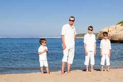 Father and sons walking on beach Stock Image