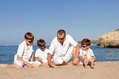 Father and sons walking on beach Stock Photo