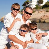 Father and sons walking on beach Stock Images