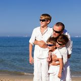 Father and sons walking on beach Stock Photography
