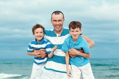 Father and sons walking on beach Royalty Free Stock Photography