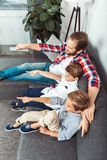 Father with sons watching tv. High angle view of smiling father with little sons watching tv together at home royalty free stock images