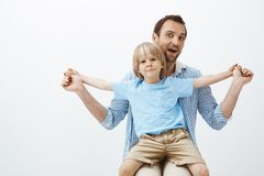 Father spending great time with cute son. Portrait of joyful good-looking european child with vitiligo, sitting on dad. Laps and spreading palms, smiling royalty free stock images