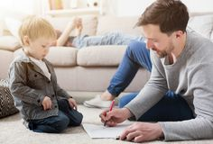 Father drawing with his little cute son. Father spending time and drawing together with his little son at home Royalty Free Stock Image