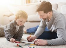 Father spending time with his little cute son. Father spending time and drawing together with his little son, lying on floor at home royalty free stock photo