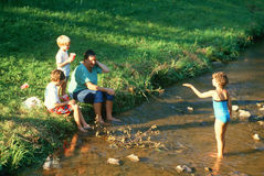 A father spending time with his children at a creek Royalty Free Stock Images