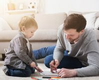 Father spending time with his little cute son. Father spending time and drawing together with his little son, lying on floor at home royalty free stock photography