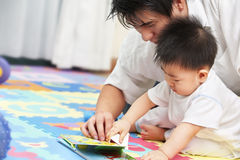 Father spending time with son. Father spending time with his little boy and tutoring him to learn reading royalty free stock photos