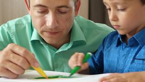 A father spends time drawing with colored pencils with his son. Passionate about the game dad and son. Happy family stock footage