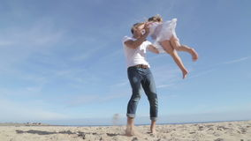 Father Spinning Daughter Round on the Beach stock footage