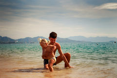 father splashes on little daughter in shallow water on beach Stock Images