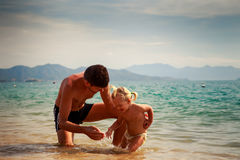 father splashes on little daughter in shallow water on beach Royalty Free Stock Photography