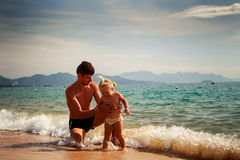 Father splashes on little daughter in shallow water on beach Stock Photography