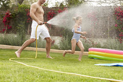 Father Spraying Daughter With Garden Hose Royalty Free Stock Photo