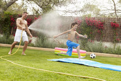 Father Spraying Son With Garden Hose Stock Photography