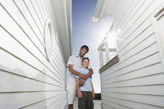 Father Standing Arm Around Son In Narrow Passageway Between Houses. Portrait of happy father standing arm around son in narrow passageway between houses Royalty Free Stock Photography