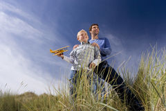 Father standing behind son (7-9 years) holding up toy airplane, standing on long grass, low angle view Royalty Free Stock Image