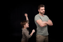 Father standing with crossed arms and little son quarreling and gesturing Stock Image