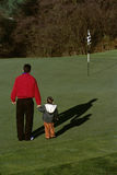 Father with his young son on a golf course Stock Photography