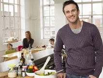 Father Standing At Kitchen Counter While Family Sitting In Background Stock Photos