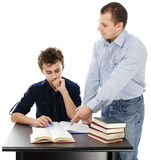 Father standing near son's desk helping him doing his homework. Studio shot of a father standing near son's desk helping him doing his homework, isolated over royalty free stock photo