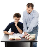 Father standing near son's desk helping him doing his homework. Studio shot of a father standing near son's desk helping him doing his homework, isolated over royalty free stock photography