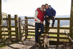 Father stands with dog, son sitting on a rural fence Royalty Free Stock Images