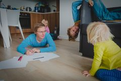 Father stays home with son and daughter, kids have fun stock photography