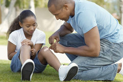 Father Sticking Bandage To Daughter's Knee At Park Stock Photo