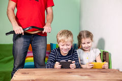 Father with strap in hands trying to grab smartphones from kids hands. Punishment a child for spending amount of time in game in c Royalty Free Stock Photography