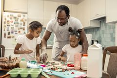 Father in striped apron helping his girls making cookies royalty free stock photography