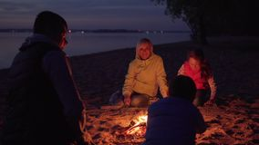 Father stroking son on head by campfire during family hike on beach. At night stock video