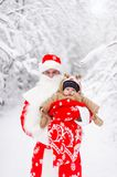 Father in suit santa claus with baby boy in a winter forest. Horizontal portrait royalty free stock photos
