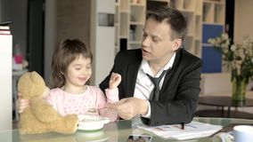 Father in suit working with papers and feeding daughter stock video footage