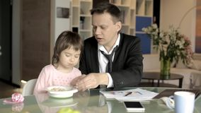 Father in suit working with papers and feeding daughter stock footage