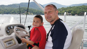 Father and son on the boat. Father teaching his son to drive the boat by letting him steer the wheel Stock Images