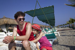 Father in sun glasses sitting near his daughter on Royalty Free Stock Photo