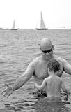 Father and Sun in Ocean. Father and toddler son swimming in ocean water with sailboats in distance royalty free stock photos