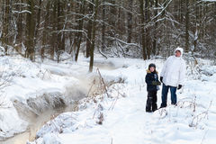 Father and sun walking in a snowy forest. Along a small river stock photo