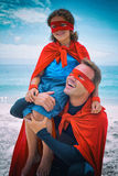 Father in superhero costume smiling while carrying son on shoulder Stock Photos