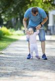 Father supporting baby daughter and helping her make first steps royalty free stock images
