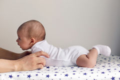 Father supports his son a newborn who lies on his stomach. On a diaper with the stars Royalty Free Stock Photos