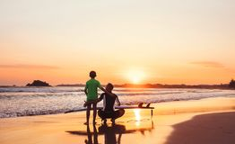 Father surfboarder with his son meet a sunset on the ocean beach Royalty Free Stock Photos