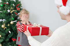 Father surprising little girl. With christmas gift Royalty Free Stock Photos