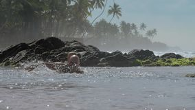 Father swims with little son on back in warm ocean water. Positive father swims with smiling little son on back in warm ocean water against rocks slow motion stock video